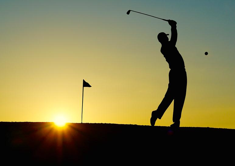 silhouette of a man playing golf at sunset
